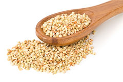 Raw, natural, uncooked buckwheat seed kernels in wooden spoon. Over white background royalty free stock photography