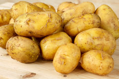 Raw new potatoes with peeling on a wooden background Royalty Free Stock Photography