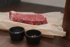 raw new york steak on walnut wood background with copy space