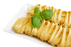 Raw noodles. On a plate with fresh basil. Isolated on white background Royalty Free Stock Photo