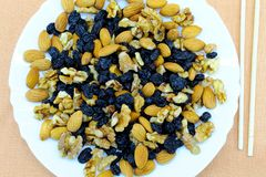 Raw nuts: almonds and walnuts. Dark dried grapes. Plus bamboo sticks stock image