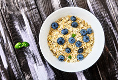 Raw oat flakes with blueberries and mint in white bowl. Top view shot of raw oat flakes topped fresh blueberries and basil leaves in white bowl. Dietary food on Royalty Free Stock Photos