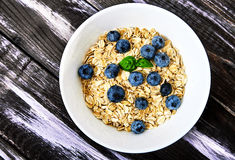 Raw oat flakes with blueberries and mint in white bowl. Top view shot of raw oat flakes topped fresh blueberries and basil leaves in white bowl. Dietary food on Royalty Free Stock Images