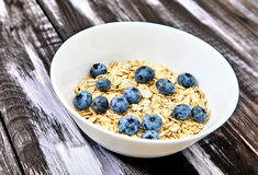 Raw oat flakes with blueberries and mint in white bowl. Top view shot of raw oat flakes topped fresh blueberries and in white bowl. Dietary food on dark wood Royalty Free Stock Images