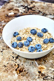 Raw oat flakes with blueberries in white bowl. Raw oat flakes topped fresh blueberries in white bowl. Organic food on metal, grunge background. Dietary, tasty Royalty Free Stock Images