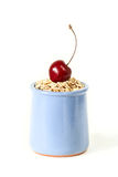 Raw oat flakes with fresh cherries. In a ceramic jar. Isolated Stock Image