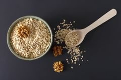 Raw oat flakes in a plate and on a dark surface. Raw porridge in a plate and on a dark surface with a wooden spoon and nuts Royalty Free Stock Photography