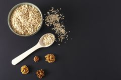Raw oat flakes in a plate and on a dark surface. Raw porridge in a plate and on a dark surface with a wooden spoon and nuts copy space Stock Photo