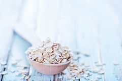 Raw oat flakes. In spoon and on a table Stock Photo