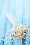 Raw oat flakes. In spoon and on a table Royalty Free Stock Image