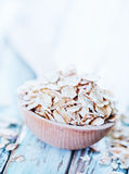 Raw oat flakes. In spoon and on a table Stock Photos