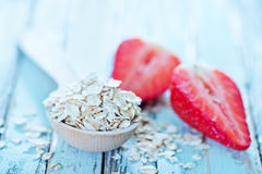 Raw oat flakes. In spoon and on a table Stock Image