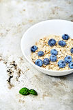 Raw oat flakes topped blueberries in white bowl. Raw oat flakes topped fresh blueberries in white bowl. Perfect ingredients for delicious and healthy breakfast Stock Image