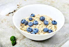 Raw oat flakes topped blueberries in white bowl. Raw oat flakes topped fresh blueberries in white bowl. Perfect ingredients for delicious and healthy breakfast Royalty Free Stock Images