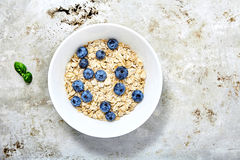 Raw oat flakes topped blueberries in white bowl. Raw oat flakes topped fresh blueberries in white bowl. Perfect ingredients for delicious and healthy breakfast Royalty Free Stock Image