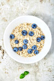Raw oat flakes topped blueberries in white bowl. Raw oat flakes topped fresh blueberries in white bowl. Perfect ingredients for delicious and healthy breakfast Stock Images