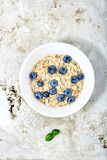 Raw oat flakes topped blueberries in white bowl. Raw oat flakes topped fresh blueberries in white bowl. Perfect ingredients for delicious and healthy breakfast Stock Photography