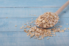 Raw oat flakes in wooden spoon Royalty Free Stock Images