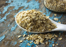 Raw oatmeal is scattered on the desk of the bank in which the oat flakes are stored. blue background in the style of Shabby Chic. White spoon with uncooked Royalty Free Stock Images
