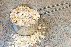 Raw Oats in a measuring cup. Raw Oats in a stainless steel measuring cup Royalty Free Stock Images