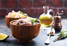 Raw octopus. In bowls and on a table Royalty Free Stock Photography