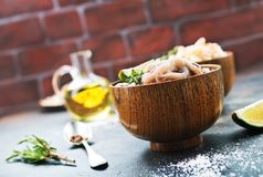 Raw octopus. In bowls and on a table Stock Photos