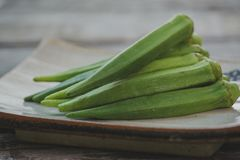 Raw okra. Farm fresh raw okra on wooden rustic table Stock Photo