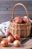 Raw onion in basket on a table, vertical Stock Photo