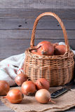 Raw onion in basket on a table, vertical Stock Photography