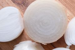Raw Onion on cutting board. Raw white onion on a cutting board with rings that are clear Stock Photo