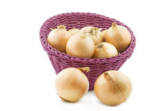 Raw onions in a basket, isolated on white Royalty Free Stock Image