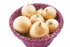 Raw onions in a basket, isolated on white Royalty Free Stock Images