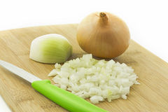 Raw onions finely hacked on a wooden board Royalty Free Stock Image
