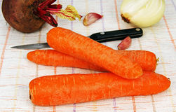 Raw orange carrot. Three pieces of crude orange carrots, beets, onions, garlic and knife on the table Royalty Free Stock Photography