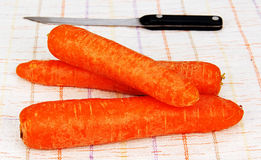 Raw orange carrot. Three pieces of crude orange carrots and knife on the table Stock Photography