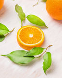 Raw Orange fruits slice with green leaves. On white wooden table Stock Image