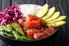 Raw Organic Ahi Tuna Poke Bowl with Rice and Veggies close-up. H. Raw Organic Ahi Tuna Poke Bowl with Rice and Veggies close-up on the table. Horizontal Royalty Free Stock Image