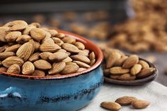 Raw Organic Almond Nuts in Bowl. Whole almonds in bowl and wooden spoon against a rustic background Royalty Free Stock Photo