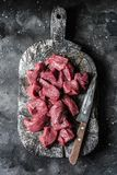Raw organic beef fillet meat pieces on wooden rustic chopping board on dark background, top view. Food ingredients. Raw organic beef fillet meat pieces on wooden royalty free stock photography
