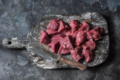 Raw organic beef fillet meat pieces on wooden rustic cutting board on dark background, top view. Food ingredients. Raw organic beef fillet meat pieces on wooden stock images