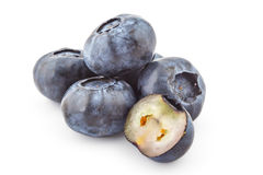 Raw organic blueberries. Three fresh ripe organic blueberries, one cutted on half, isolated on a white background Royalty Free Stock Images