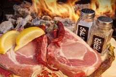 Raw Organic Bone Steaks with spice near BBQ Grill, XXXL Stock Photos