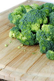 Raw Organic Broccoli on a Wooden Cutting Board. Raw Organic Broccoli cut up in pieces on a wooden cutting board royalty free stock image