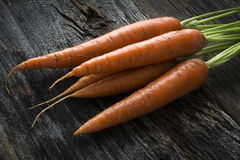Raw Organic Carrots with Greens on Wood Stock Photos