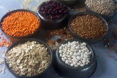 Raw organic cereal grains, seeds and beans & x28;millet, rye,wheat, buckwheat, red and white beans, lentil, rice& x29;. In metall bowls on light background Stock Photography