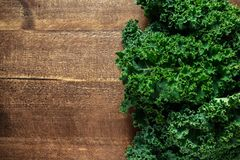 Raw organic freshly picked green curly kale on wooden table Stock Photos