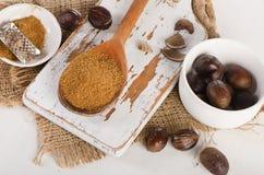 Raw Organic ground  Nutmeg on  white wooden cutting board. Stock Photo