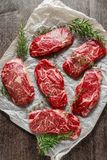 Raw organic Marbled beef steaks with rosemary and thyme on cooking paper.  Stock Image