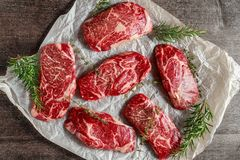 Raw organic Marbled beef steaks with rosemary and thyme on cooking paper.  Stock Photos
