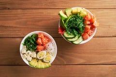 Raw Organic Poke Bowl with with rice, avocado, salmon, mango, cucumbers, chuka salad, quail eggs, sweet onions two plates close-up stock photo